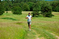 Young man with headphones jogging in a meadow