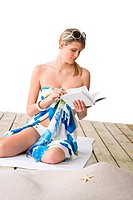 Beach _ woman sitting with book, sunbathing