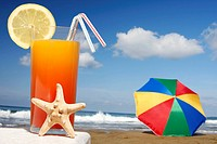 Tropical cocktail with starfish with parasol and beach