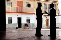 Silhouette of two men talking in an old street, Utrera, Sevilla, Andalucia, Spain, Europe