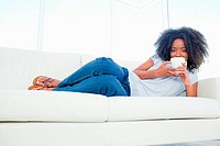 Portrait of a fuzzy hair woman drinking a coffee while lying on her sofa