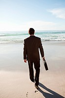 Rear view of a serious businessman walking on the beach while holding a briefcase