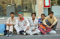 male workers lined up on a street rest at the end of a working day  dubai  dubai  uae  middle east
