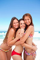 Thre friends smiling while hugging each other as they stand on the beach in bikinis