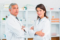 Two pharmacists with their arms folded in the pharmacy of a hospital