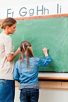 Elementary teacher and student writing on blackboard together