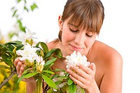 Portrait of woman smelling blossom of Rhododendron