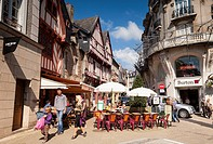 Street scene in the old city of Vannes, Brittany, France  In the foreground, a young man, woman and boy, a pavement cafe with a seniot couple, and in ...