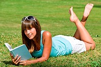Smiling woman lying down on grass with book