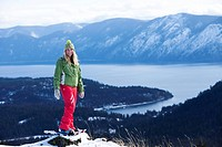 A beautiful young woman smiles while snowshoeing above a lake in Idaho.