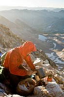 A man making coffee on the summit of Capitol Peak, White River National Forest, Aspen, Colorado.