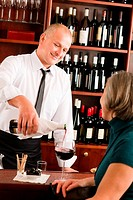 Wine bar waiter serving senior woman glass