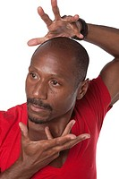 Studio portrait of mid adult African American male dancer performing on white background