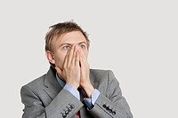 Close_up of a shocked businessman with hands covering mouth over light gray background