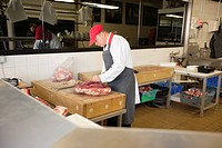 Mature man cutting beefsteak in butcher shop