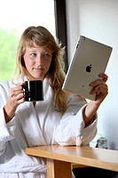 Young woman in the morning in the kitchen, in bathrobe and with a cup of coffee, reading on an iPad, tablet computer, an on-line newspaper