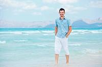 young man walking near blue sea.