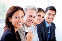 Team of happy businesspeople sitting in a row and smiling at the camera _ portrait