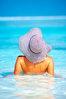Rear view of relaxed beauty wearing sun hat in water
