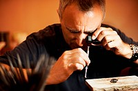 Jeweler examining a gemstone through a magnifying glass