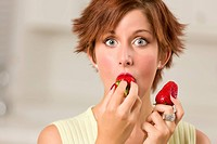 Pretty Wide_eyed Red Haired Woman Biting Strawberry