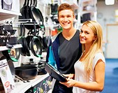 Young couple smiling at the camera while holding a frying pan in a homeware store