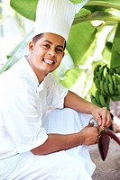 Portrait of happy young cook at banana tree in garden