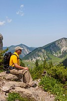 Hiker, 56 years, sitting on rocks enjoying the view, Taubenstein near Spitzingsee lake, Mangfall Mountains, Alps, Bavaria, Germany, Europe