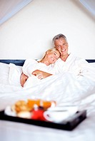 Portrait of a happy mature couple on bed with breakfast in front