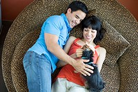Couple laying together petting dog