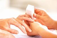 Closeup of a manicurist pampering a female´s nails