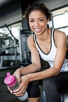 Mixed race woman drinking water in health club