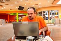 Man with laptop in restaurant