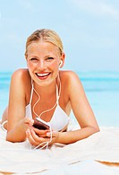 Portrait of pretty young woman listening to music on cellphone at beach