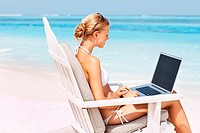 Portrait of young woman surfing internet while sitting on deck chair