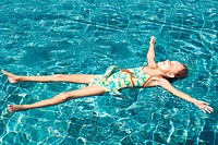 Cute young girl floating in a clear swimming pool