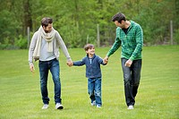 Boy walking with two men in a park