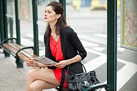 Woman sitting at a bus stop and holding a newspaper (thumbnail)
