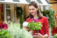 Woman holding a potted plant in a flower shop (thumbnail)