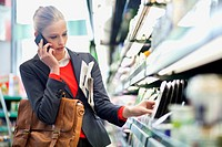 Woman in a supermarket talking on a mobile phone (thumbnail)