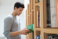 Man choosing a book from a bookshelf (thumbnail)