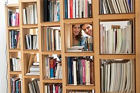 Couple peeking from a hole of a bookshelf