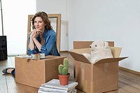 Woman leaning on a cardboard box and smiling (thumbnail)