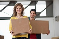 Couple carrying cardboard boxes and smiling