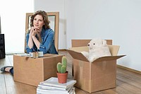 Woman leaning on cardboard box and thinking