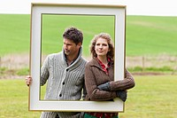 Couple holding a frame in a field