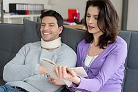 Woman reading a book for her husband suffering from neckache (thumbnail)