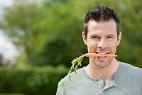 Man holding a carrot in his mouth