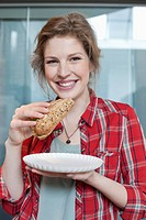 Portrait of a woman eating sandwich and smiling