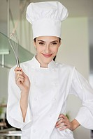 Happy female chef holding a wire whisk